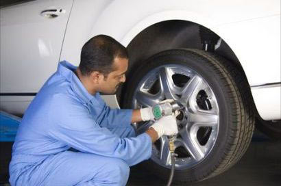auto mechanic changing a tire in a car